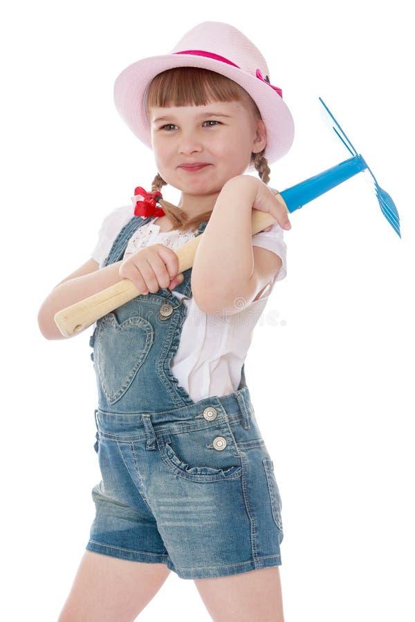 Bambina che tiene un rastrello fotografia stock