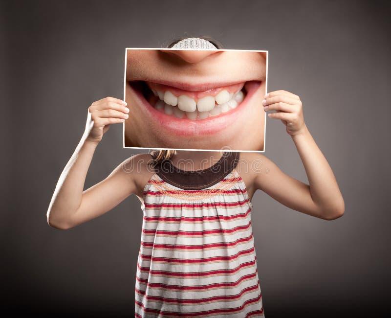 Bambina che tiene un sorriso fotografia stock libera da diritti