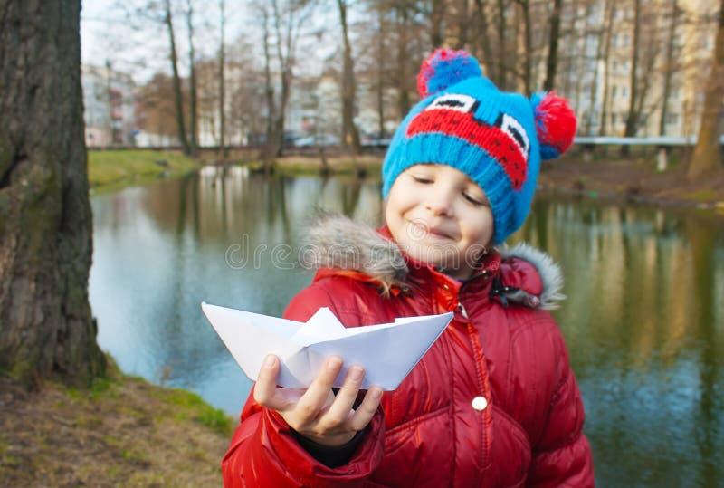 Bambina che tiene una barca di carta vicino al fiume