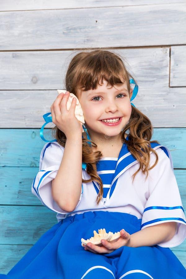 Bambina che tiene una conchiglia e le risate fotografia stock libera da diritti