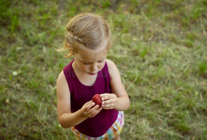 Bambina che tiene una fragola rossa fotografia stock libera da diritti