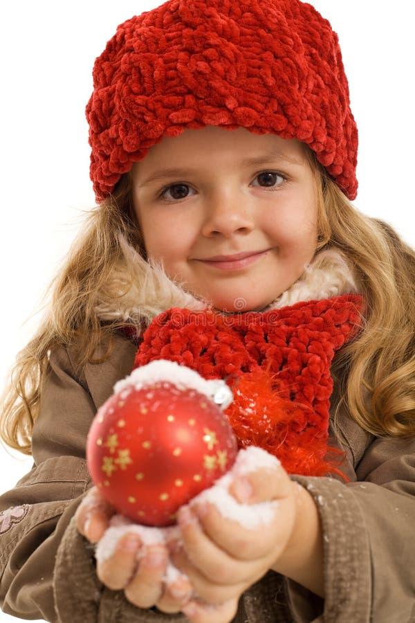 Bambina che tiene una sfera di natale in neve fotografia stock