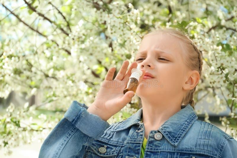 Bambina che usando le gocce nasali vicino all'albero di fioritura Concetto di allergia fotografia stock libera da diritti