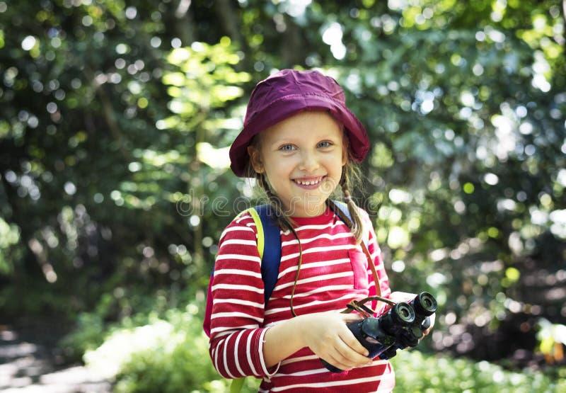 Bambina che utilizza il binocolo nella foresta fotografia stock libera da diritti