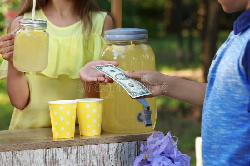 Bambina che vende limonata naturale al ragazzo afroamericano in parco Bevanda di rinfresco di estate fotografia stock