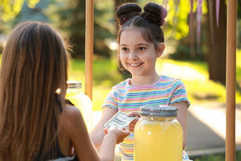 Bambina che vende limonata naturale per scherzare in parco fotografia stock