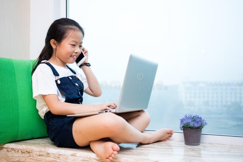 Bambina cinese asiatica che discute a fondo telefono con il computer portatile immagine stock libera da diritti