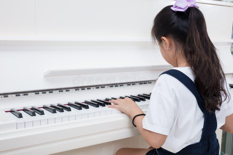 Bambina cinese asiatica che gioca piano classico a casa immagine stock libera da diritti