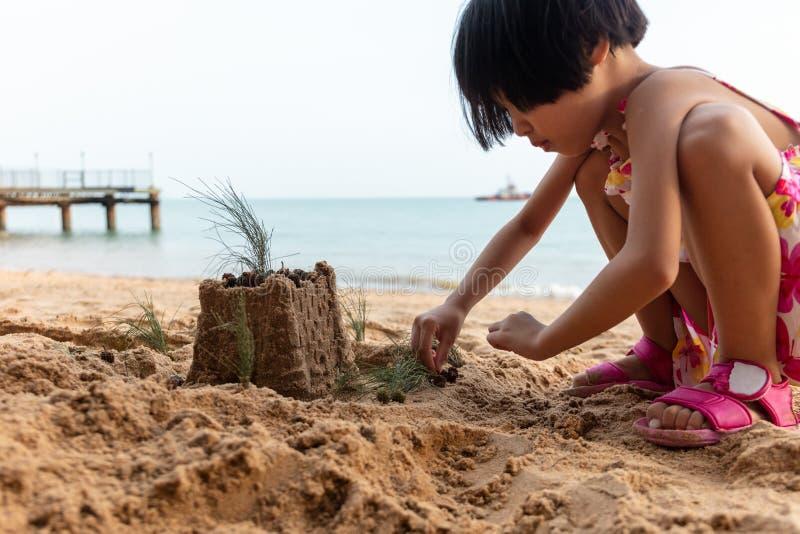 Bambina cinese asiatica che gioca sabbia alla spiaggia fotografia stock libera da diritti