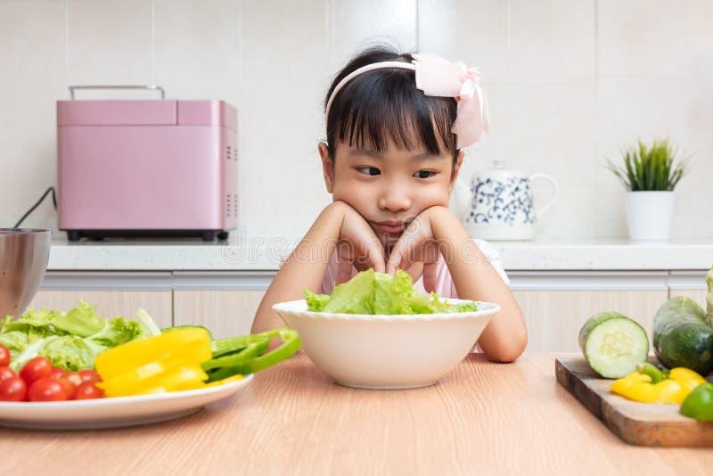 Bambina cinese asiatica che mangia insalata nella cucina fotografia stock libera da diritti