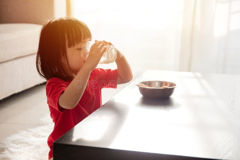 Bambina cinese asiatica che mangia prima colazione con latte immagini stock