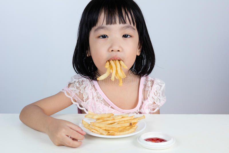 Bambina cinese asiatica che rifiuta mangiando le patate fritte immagine stock libera da diritti