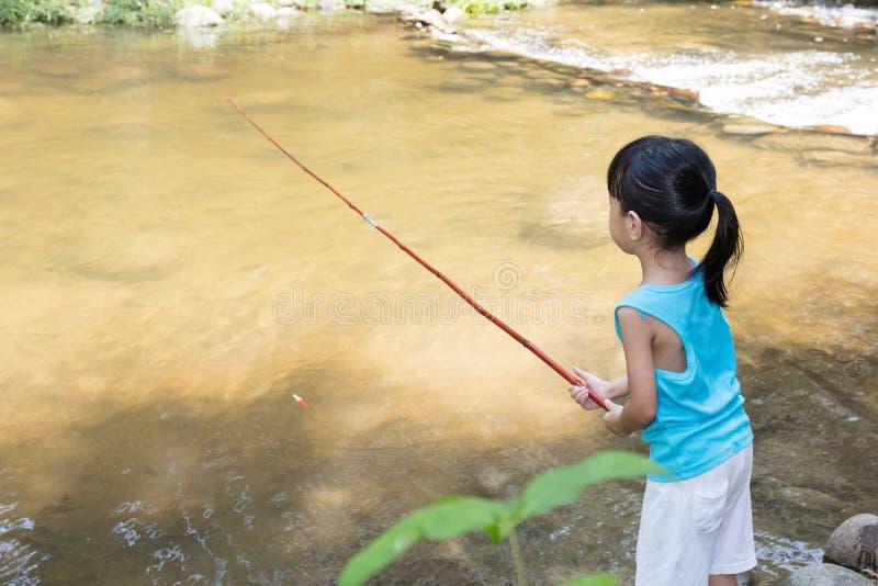 Bambina cinese asiatica che si inclina con la canna da pesca immagini stock libere da diritti