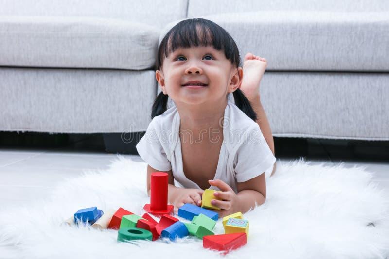 Bambina cinese asiatica felice che gioca i blocchi sul pavimento fotografia stock