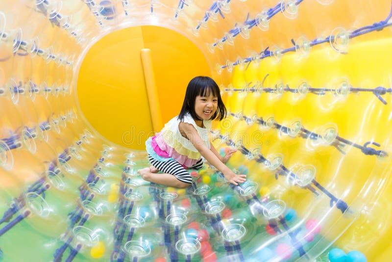 Bambina cinese asiatica felice che gioca la ruota del rullo fotografie stock libere da diritti