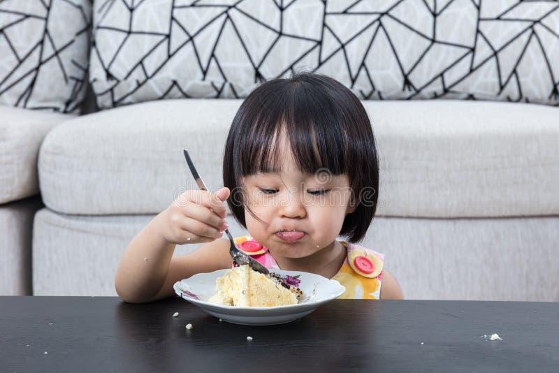 Bambina cinese asiatica lunatica che mangia la torta di formaggio di compleanno fotografia stock