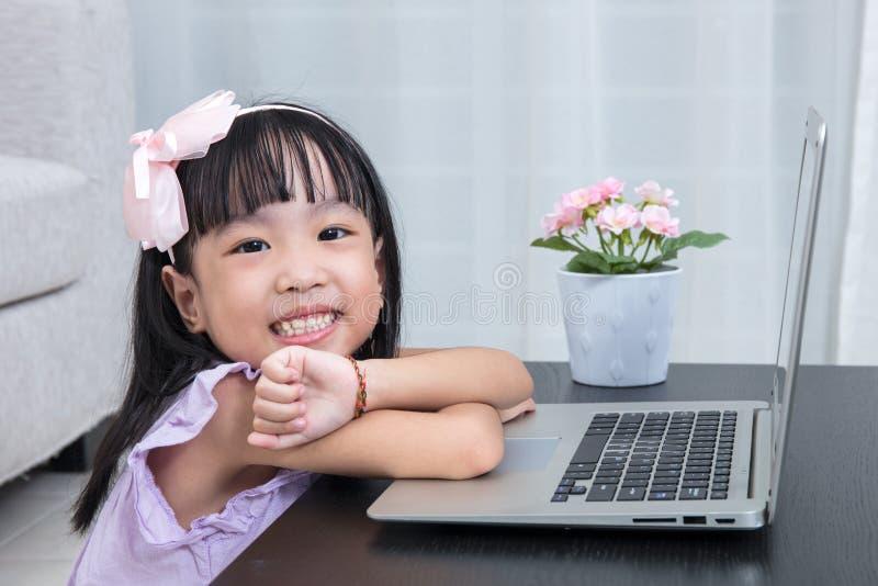 Bambina cinese asiatica sorridente che per mezzo del computer portatile a casa immagine stock