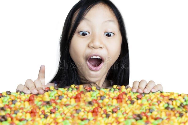 Bambina colpita che esamina le caramelle immagine stock