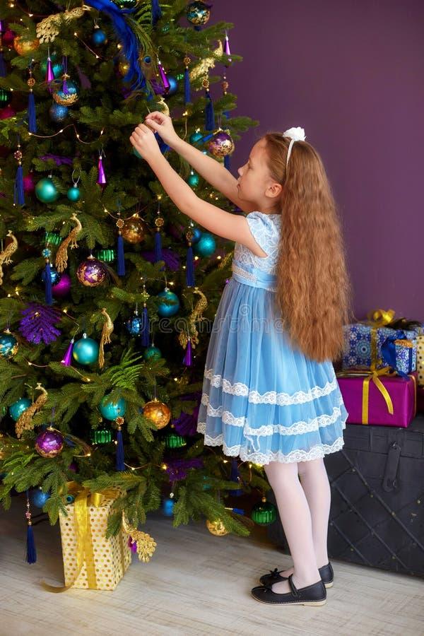 Bambina con capelli lunghi che decora l'albero di Natale fotografia stock