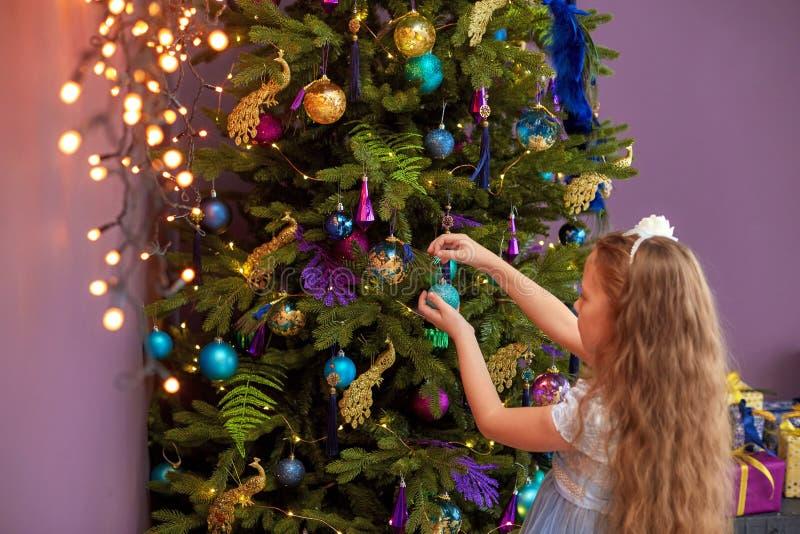 Bambina con capelli lunghi che decora l'albero di Natale immagini stock
