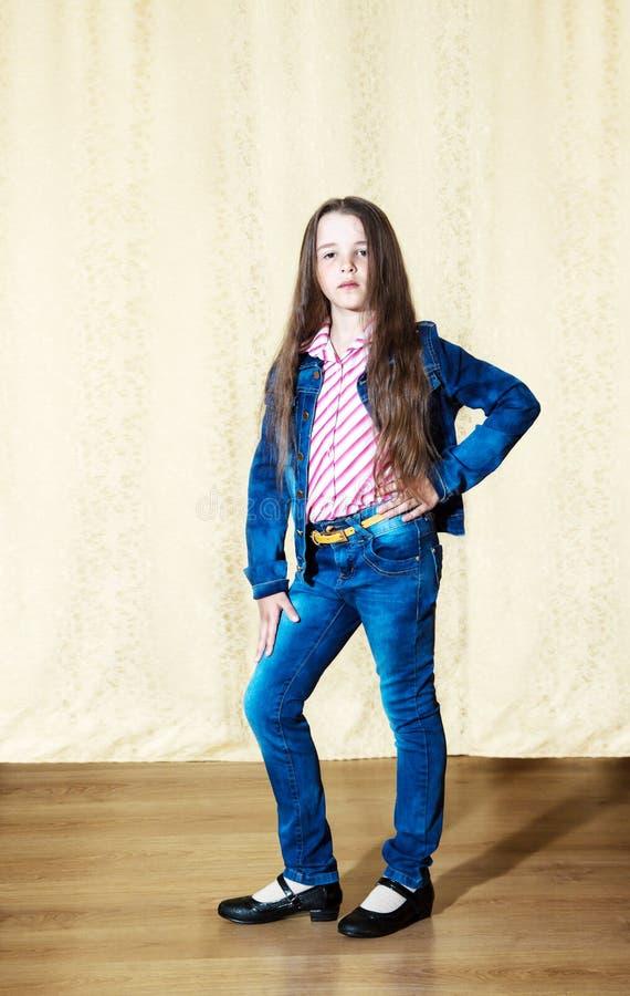 Bambina con capelli lunghi in un vestito blu del denim