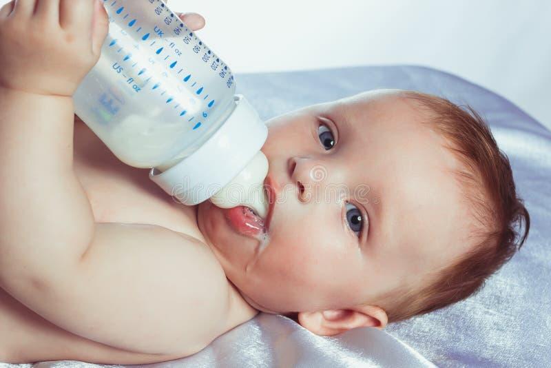 Bambina con gli occhi azzurri che si trovano in pannolini fotografia stock