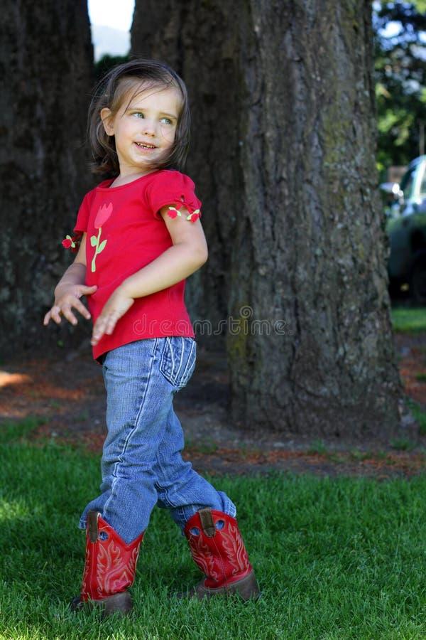 Bambina con i caricamenti del sistema di cowboy rossi fotografie stock libere da diritti