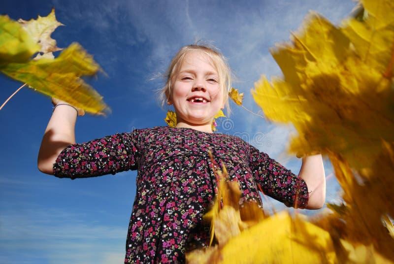 Bambina con i fogli di autunno fotografie stock