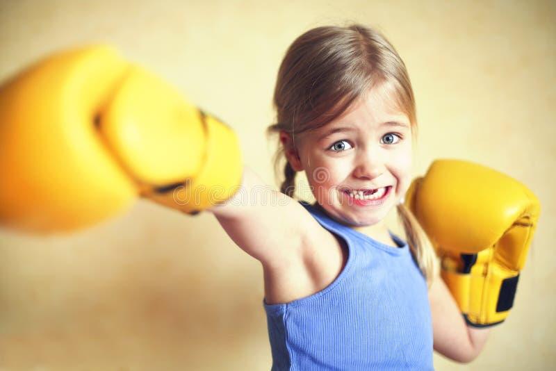 Bambina con i guantoni da pugile gialli sopra il backgroun giallo della parete fotografie stock