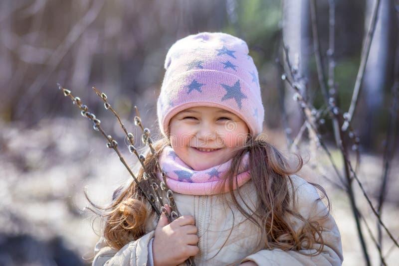 Bambina con i ramoscelli del salice nella foresta in primavera immagini stock libere da diritti