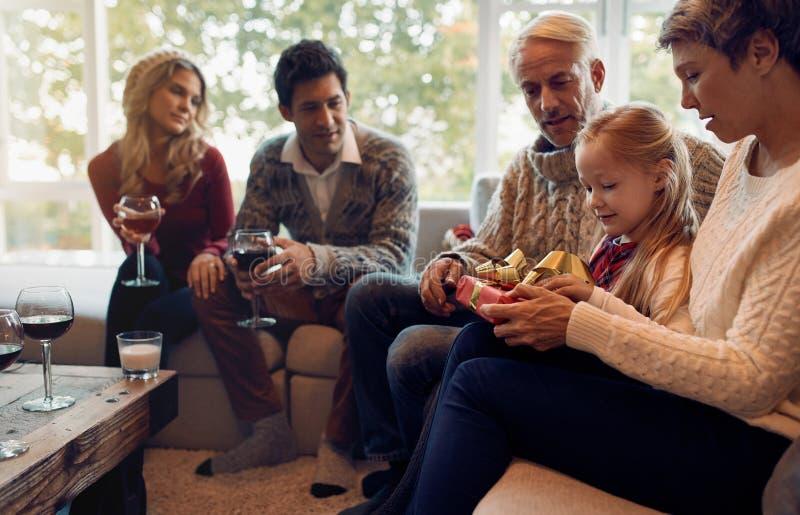 Bambina con i regali di natale di apertura della famiglia fotografia stock