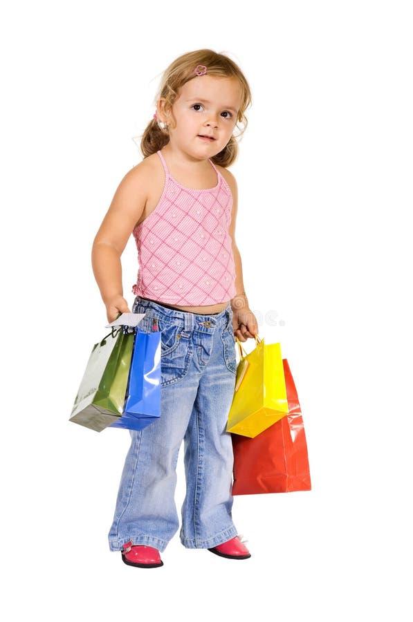 Bambina con i sacchetti di acquisto variopinti fotografia stock