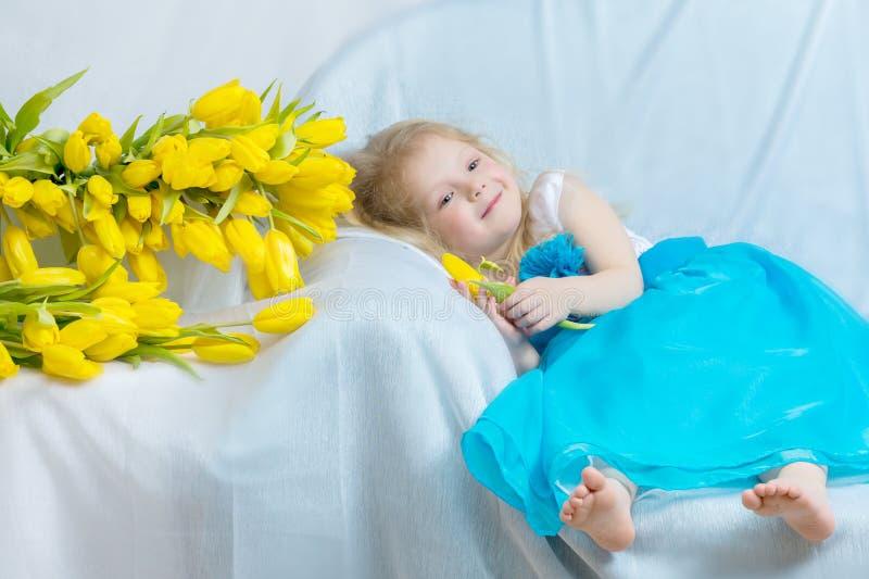 Bambina con i tulipani gialli fotografia stock