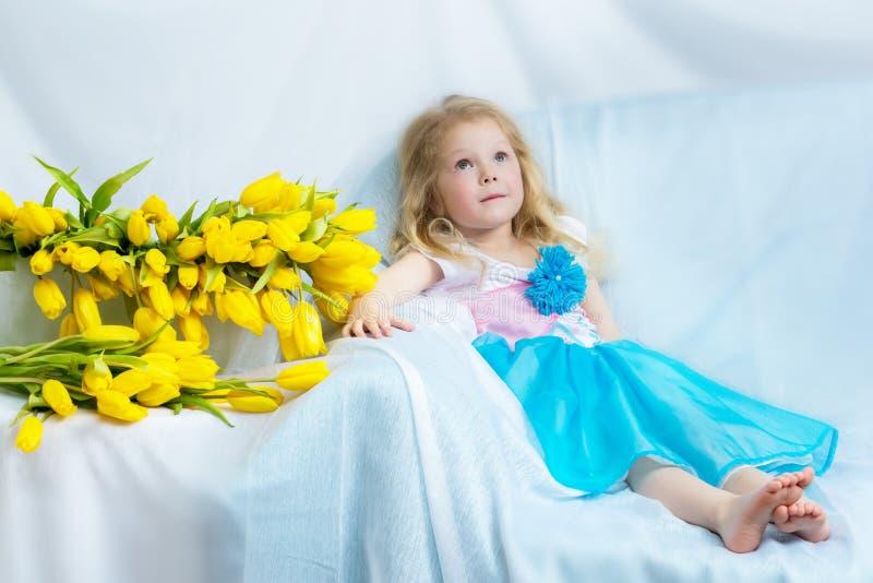 Bambina con i tulipani gialli fotografia stock libera da diritti
