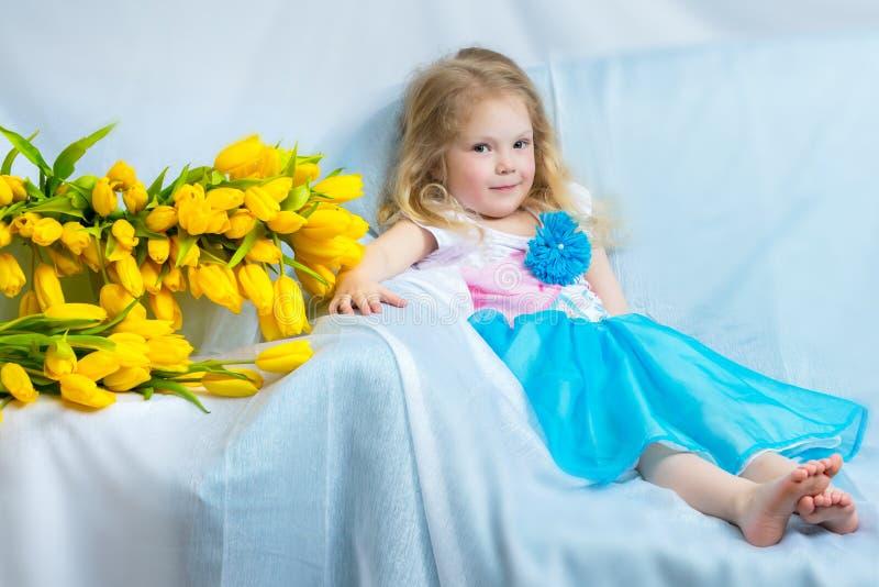 Bambina con i tulipani gialli immagine stock