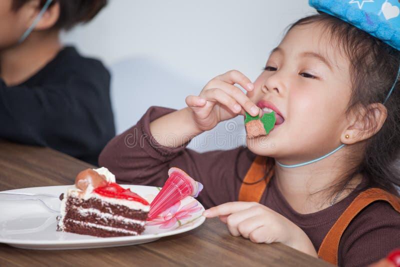Bambina con il cappello che mangia torta di compleanno immagine stock