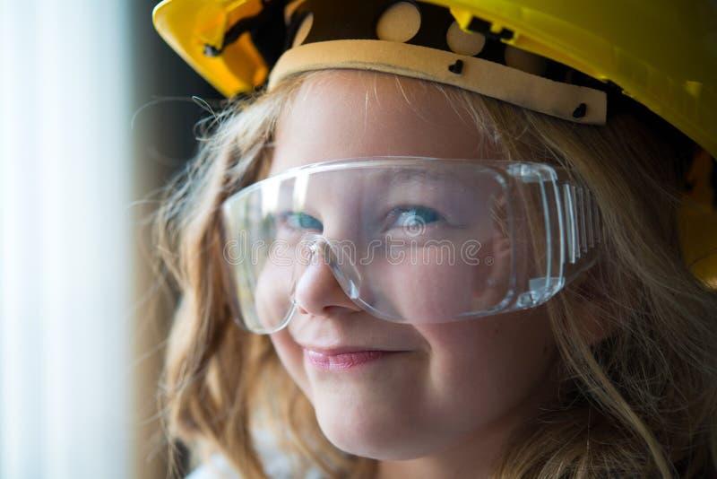 Bambina con il casco e gli occhiali di protezione di sicurezza immagini stock libere da diritti