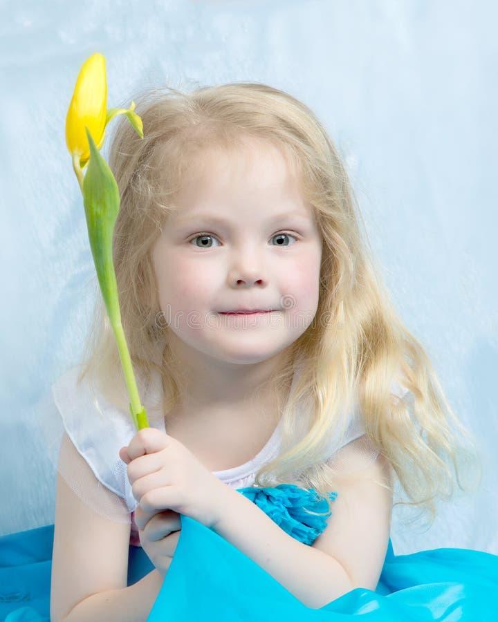 Bambina con il fiore giallo immagine stock