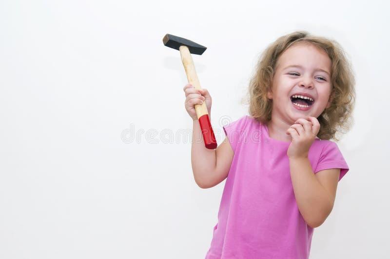 Bambina con il martello ed il sorriso immagine stock