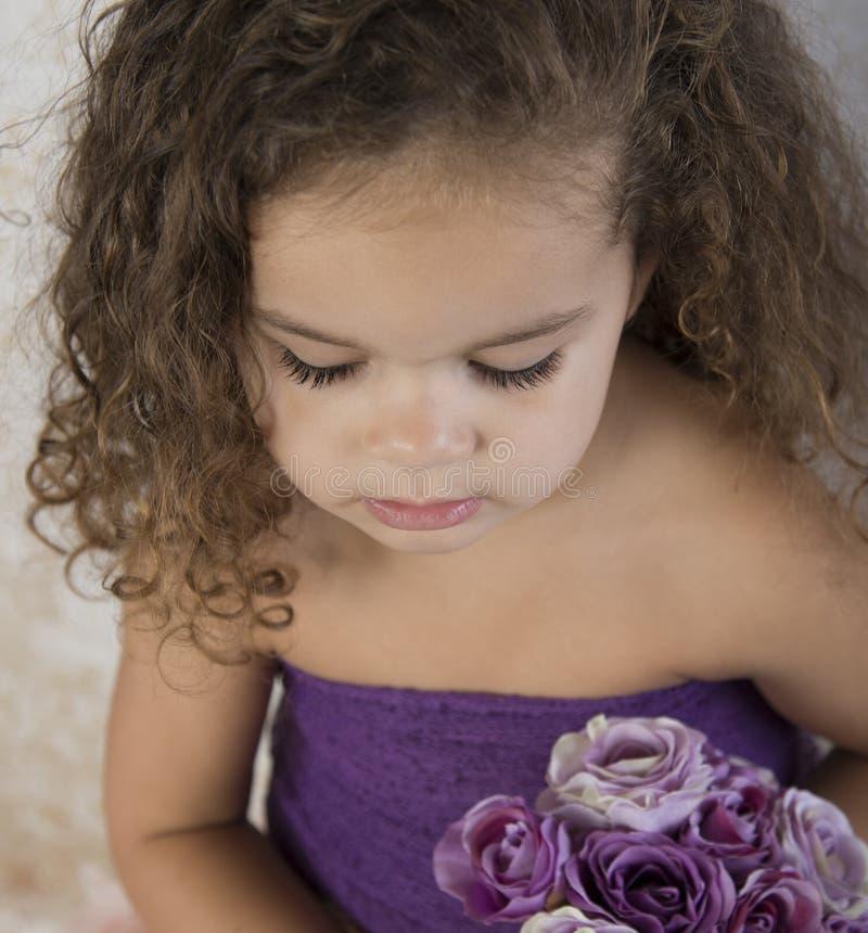 Bambina con il mazzo dei fiori porpora fotografia stock