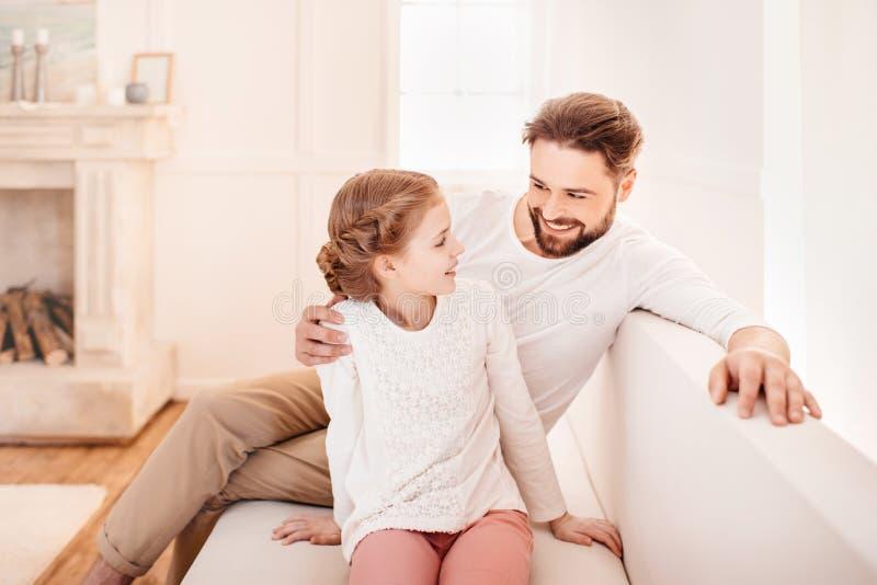 Bambina con il padre che si siede insieme sul sofà e che si sorride immagini stock libere da diritti