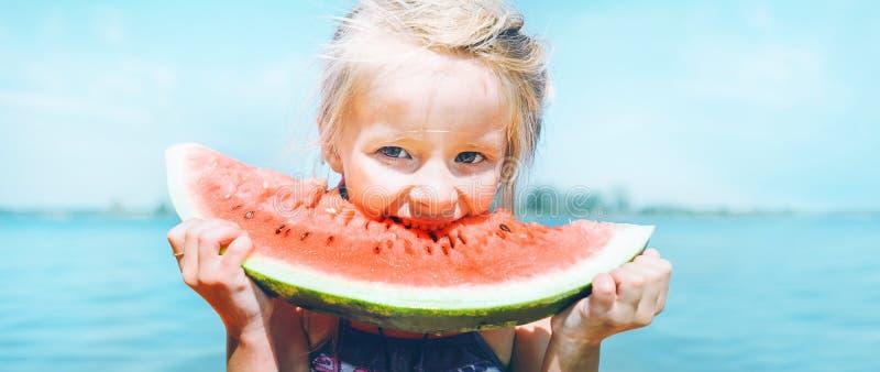 Bambina con il ritratto divertente di grande segmento dell'anguria Immagine sana di concetto di cibo fotografia stock