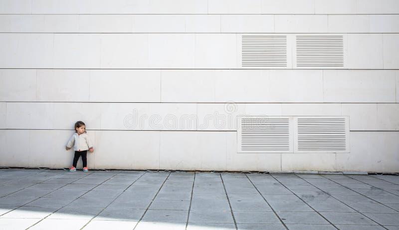 Bambina con il sembrare allegro che posa sopra la parete fotografia stock libera da diritti
