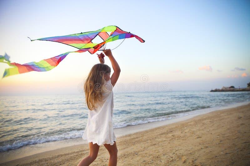 Bambina con l'aquilone di volo sulla spiaggia tropicale al tramonto immagine stock
