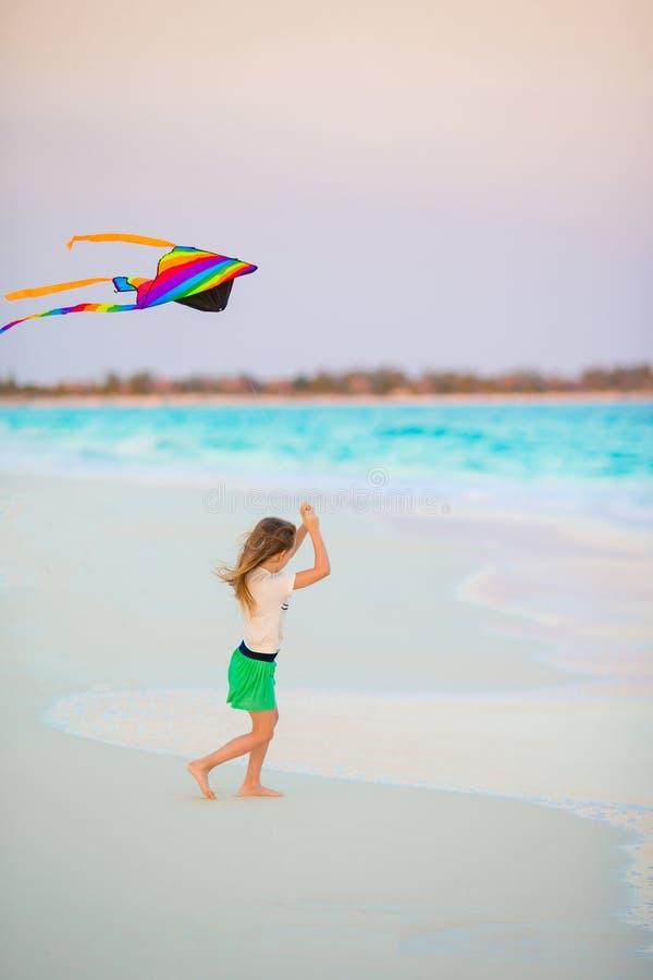 Bambina con l'aquilone di volo sulla spiaggia tropicale Gioco del bambino sulla riva dell'oceano Bambino con i giocattoli della s fotografie stock
