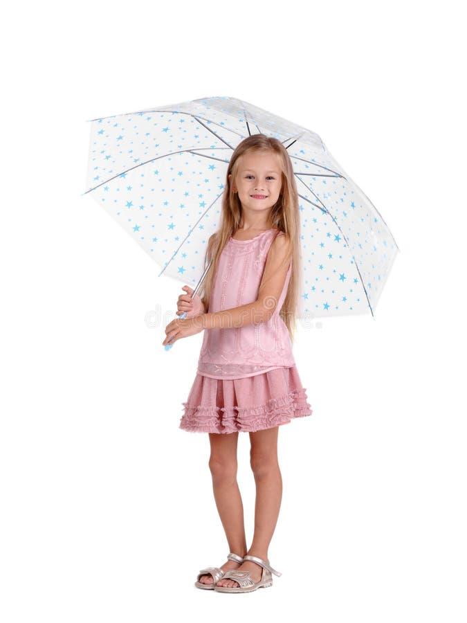 Bambina con l'ombrello Una ragazza prescolare sveglia in un vestito rosa isolato su un fondo bianco Il bambino copre il concetto fotografia stock libera da diritti