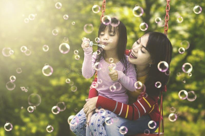 Bambina con la madre che gioca le bolle di sapone immagini stock libere da diritti