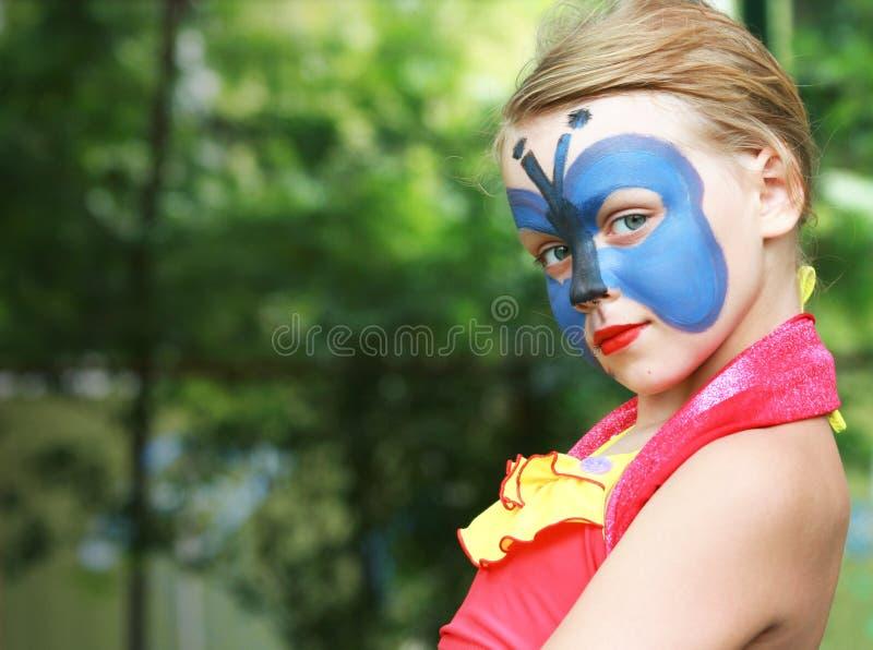 Bambina con la mascherina blu verniciata della farfalla fotografie stock