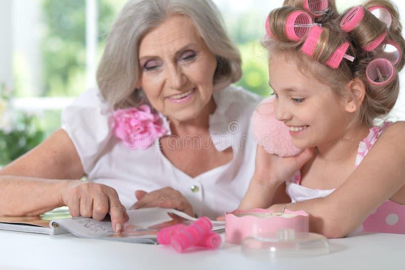 Bambina con la nonna con la rivista e lo smalto fotografia stock libera da diritti