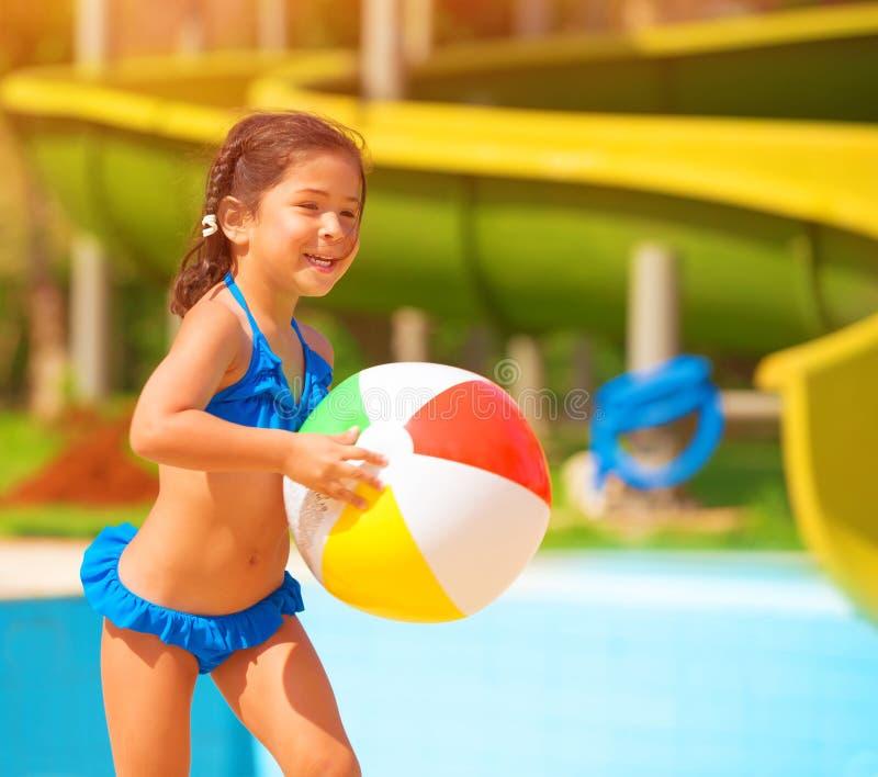 Bambina con la palla vicino allo stagno fotografia stock